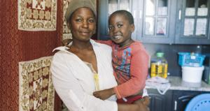 A mother holds her young child while smiling and facing the camera in a medical center that targets Malaria