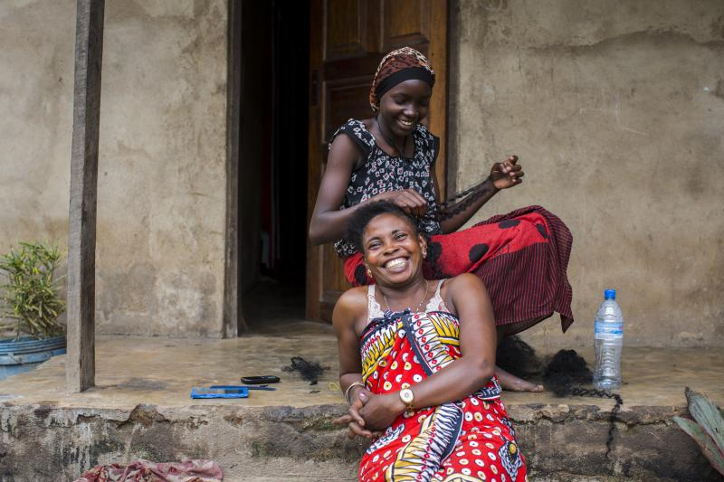 Two women laugh as they sit on steps outside a building