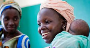 A woman laughs as she holds her baby in a primary healthcare center