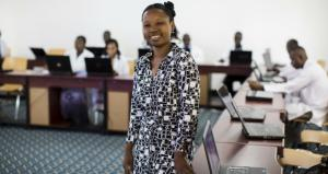 A woman stands in the center of a room surrounded by people with laptops in Tanzania